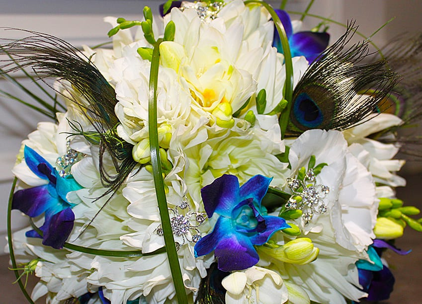white dahlias, white freesia, blue orchids, bear grass, peacock feathers, jewels